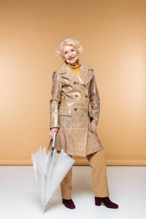 fashionable senior woman in trench coat with umbrella