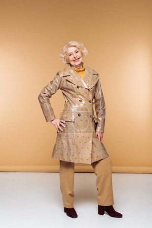 happy stylish senior woman posing in trench coat
