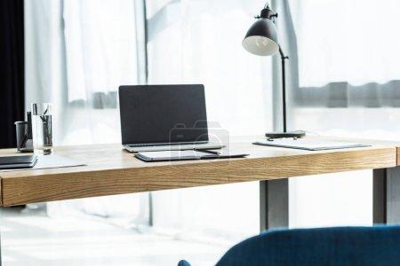Foto de Lugar de trabajo con ordenador portátil y varias fuentes en la oficina moderna - Imagen libre de derechos