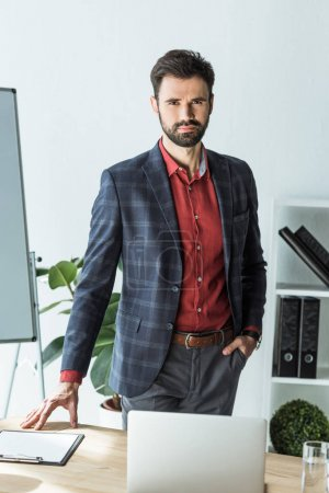 attractive young businessman standing next to his workplace at office