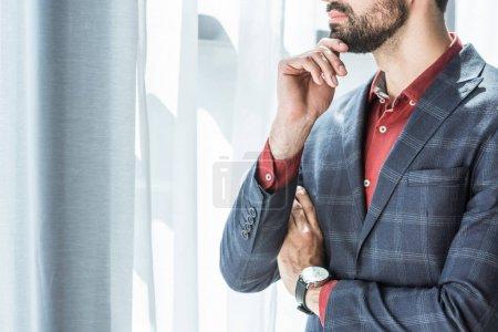 Photo pour Recadrée tir du jeune homme d'affaires avec la main sur le menton, regardant par la fenêtre - image libre de droit