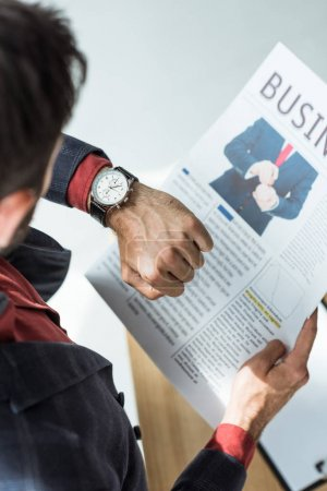 Photo for High angle view of businessman reading newspaper and looking at watch at office - Royalty Free Image