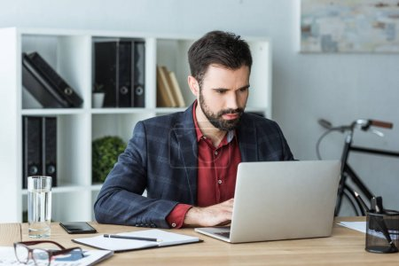 handsome young businessman working with laptop at office