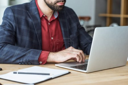 cropped shot of businessman working with laptop at office