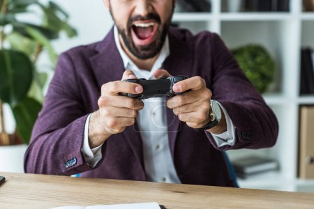 cropped shot of shouting young businessman playing games with gamepad