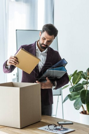 dismissed young businessman putting books and folders into box