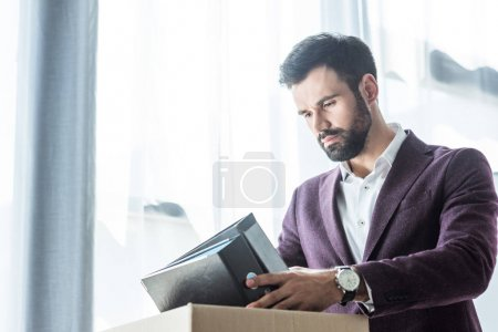thoughtful young businessman putting books and folders into box after he gets fired