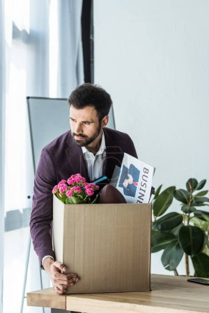 dismissed businessman taking box of personal stuff from desk at office