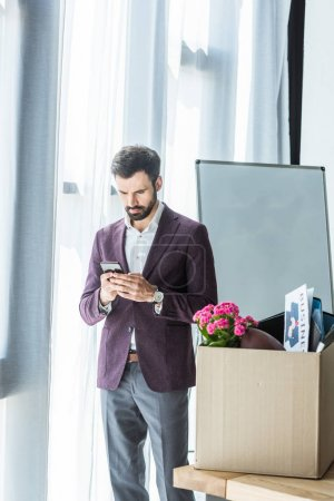 fired young businessman using smartphone near box of personal stuff at office