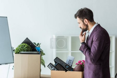 side view of thoughtful young businessman looking at boxes of personal stuff after he gets fired