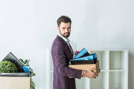 side view of fired young businessman carrying box of personal stuff at office