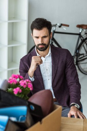 thoughtful young businessman sitting in office and looking at box of personal stuff after he gets fired