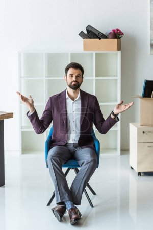 bewildered young businessman sitting on chair in office after he gets fired