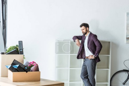 thoughtful fired businessman leaning on shelves at office