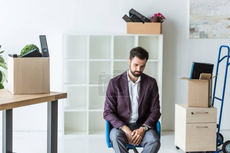 depressed fired businessman sitting on chair in office with boxes of personal stuff
