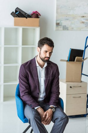 depressed fired businessman sitting on chair in empty office
