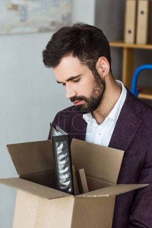 close-up shot of depressed young businessman with box of personal stuff after he gets fired