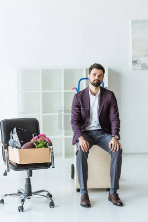 dismissed young businessman with box of personal stuff sitting on trolley cart