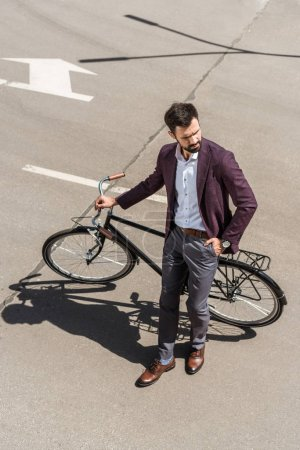 high angle view of stylish young businessman with vintage bicycle
