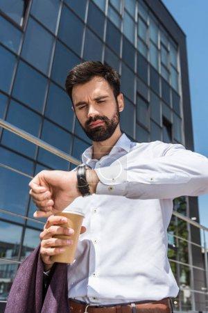 Photo pour Vue de dessous du beau jeune homme d'affaires avec café pour aller chercher à la montre-bracelet - image libre de droit