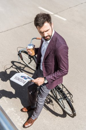 high angle view of handsome young businessman with coffee to go and newspapers leaning back on bicycle