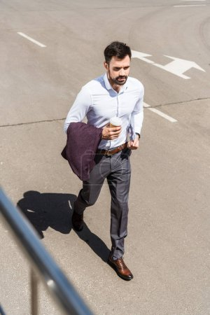 Photo for High angle view of handsome young businessman with paper cup of coffee running for work - Royalty Free Image