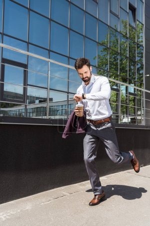Photo for Handsome young businessman with paper cup of coffee running for work - Royalty Free Image