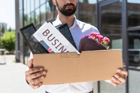 cropped shot of young manager with box of personal stuff outdoors after he was fired