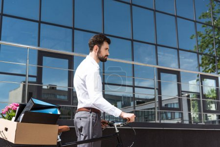 depressed young manager with box of personal stuff on bicycle looking away