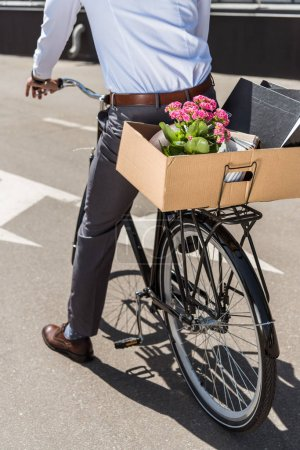 cropped shot of manager riding on bicycle with box on trunk