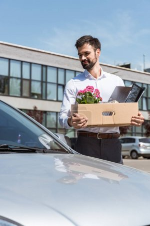 happy young manager with box of personal stuff standing near car on parking