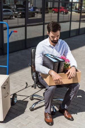 young sad dismissed manager with box of personal stuff sitting on chair outdoors