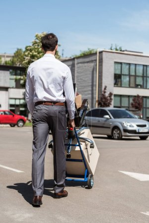 rear view of fired young manager with boxes on trolley cart at parking