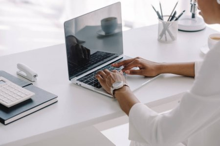 cropped image of african american businesswoman using laptop in workspace