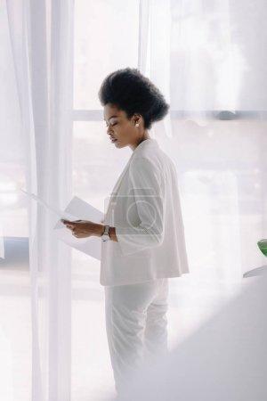 Photo pour Vue latérale d'une séduisante femme afro-américaine lecture des documents au bureau - image libre de droit