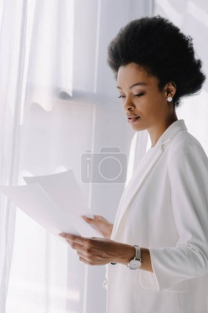 attractive african american businesswoman reading documents in office