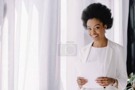 Photo pour Attrayante femme afro-américaine souriante munies de documents de bureau - image libre de droit