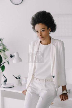 Photo pour Attrayante femme afro-américaine se penchant sur la table et en regardant la caméra dans le Bureau - image libre de droit