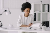 attractive african american businesswoman reading notes in notebook in office