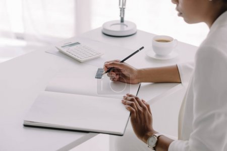 cropped image of african american businesswoman writing something to notebook in office