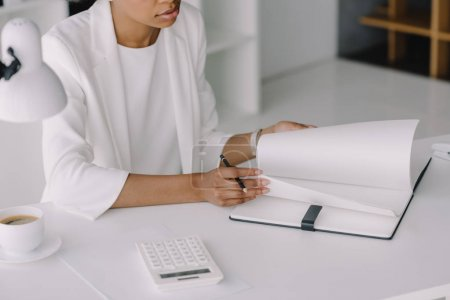 cropped image of african american businesswoman working at table in office
