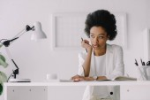 beautiful pensive african american businesswoman sitting at table and looking away in office