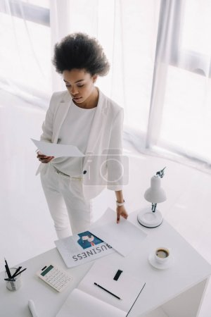 high angle view of attractive african american businesswoman reading document in office