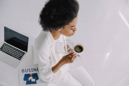 high angle view of attractive african american businesswoman sitting on table with cup of coffee in office