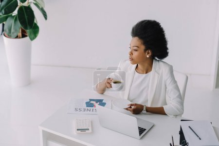 Photo for High angle view of attractive african american businesswoman holding cup of coffee in office - Royalty Free Image