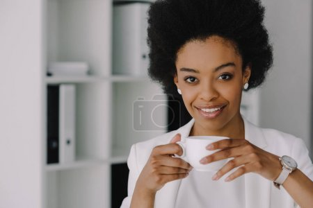 attractive african american businesswoman holding cup of coffee and looking at camera in office