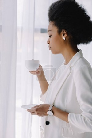attractive african american businesswoman holding cup of coffee in office