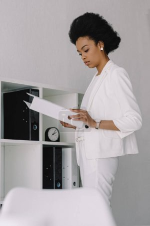 Photo for Attractive african american businesswoman holding folder with documents in office - Royalty Free Image