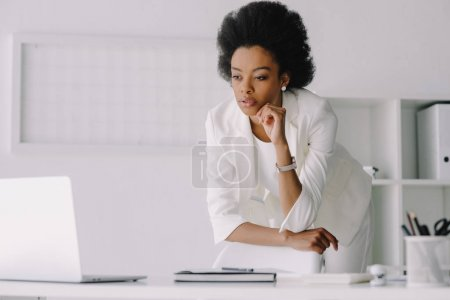attractive african american businesswoman leaning on table and looking at laptop in office