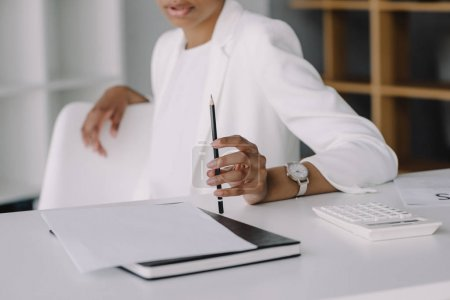 Photo for Cropped image of african american businesswoman sitting at table and holding pencil in office - Royalty Free Image
